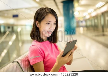 Woman use of smart phone at train platform