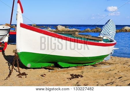 closeup of an old fishing boat stranded on the Platja de les Barques beach in Calella de Palafrugell, Costa Brava, Catalonia, Spain
