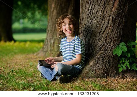 The cheerful boy sits under a tree with the tablet on a lap and puts out the tongue. In ears earphones. Jeans are torn on a lap.Behind the back there is a thick tree trunk.