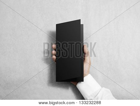 Hand holding blank black opened brochure booklet in the hand. Leaflet presentation. Pamphlet hold hand. Man show flyer offset paper. Sheet template. Booklet design. Paper display read first person