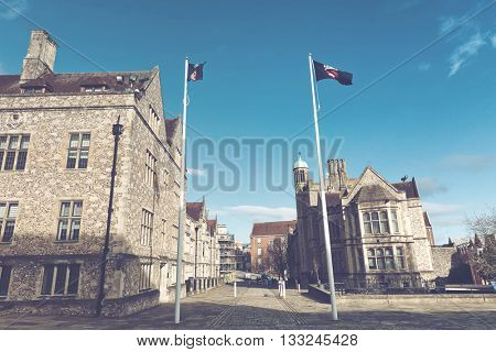 WINCHESTER, UK - FEBRUARY 07: Fluttering flags on flagpoles high up waving in air at front of British historical landmarks from medieval era. Winchester, UK on February 07, 2016.