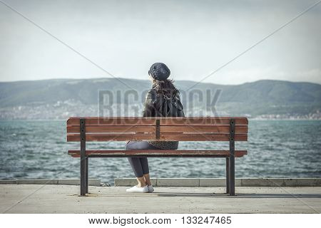 Woman sitting on the bench near the sea.