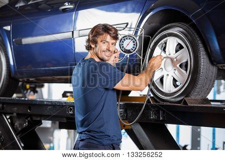 Mechanic Holding Gauge While Inflating Car Tire