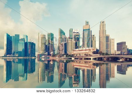 Singapore central quay with reflection on foreground. Modern city architecture at sunrise.