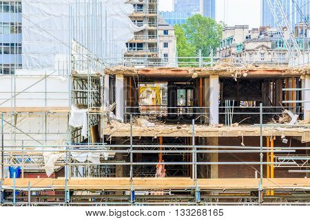 Building constriction site with scaffolding cranes and industrial unites