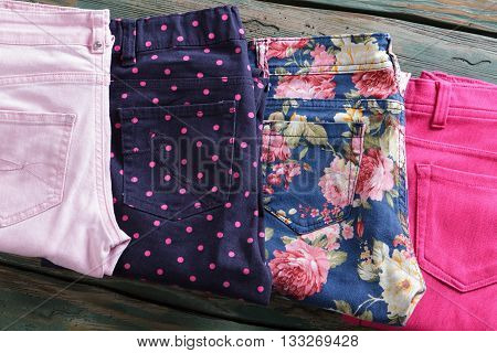 Blue floral pattern pants. Folded bright pink trousers. Woman's pants in outlet store. Newly purchased clothing on shelf.