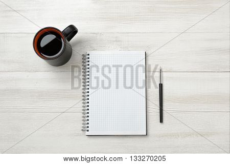 Notebook, cup of coffe and pencil put on table. Tools of writing. Studing and authorship. Marketing plan. Business planning.