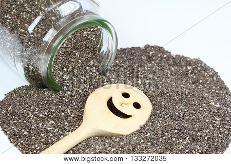 Organic dry chia seeds. Glass of chia seeds. Chia seeds on white background. Chia seeds with funny stirring spoon. Healthy chia seeds. Seeds of salvia hispanica.