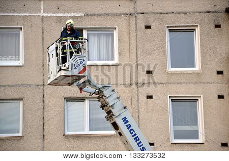 Bytca, Slovakia - June 4, 2016: Firefighter uprise into telescopic boom basket of fire truck block of flats in background