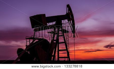Sunset sky with profiled oil well, in remote European oil and gas field
