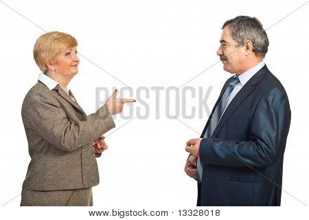 Mature business woman pointing to his colleague man and smiling isolated on white background poster