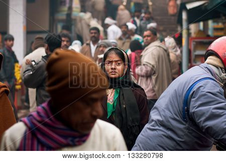 UTTAR PRADESH, INDIA - JAN 27, 2013: Beautiful Indian woman looking for someone in the crowd of people on January 27, 2013 in India. Uttar Pradesh is the 5th largest state with 200 million people