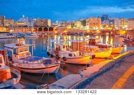 Old harbour of Heraklion with fishing boats and marina during twilight blue hour, Crete, Greece. Boats blurred motion on the foreground.
