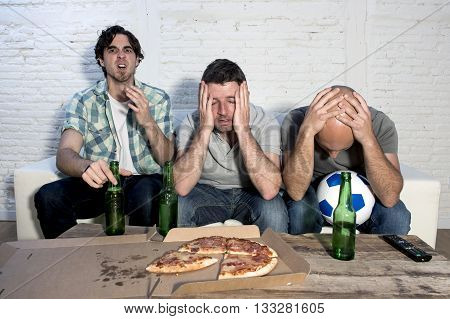 group of friends fanatic football fans watching soccer game on television with beer bottles and pizza suffering stress and crazy nervous on couch sad and dejected as if their team is loosing