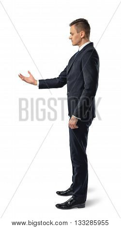 Side view of businessman holding something in his hand in front of him, isolated on white background. Successful lifestyle. Business staff. Office clothes. Dress code. Presentable appearance. Self-confidence.