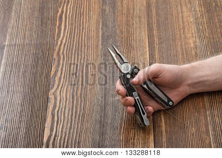 Close-up hands of man holding multitool on a wooden background. All-in-one. Universal tool for everybody. Convenient and compact everyday instrument. Improved construction tools. Modern everyday instruments and tools.