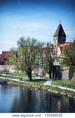 Tranquil Scenic of Walking Paths on Banks of River Blau in front of Walled City with View of Historical Metzgerturm Butcher Tower on Sunny Spring Day with Blue Vignette Sky