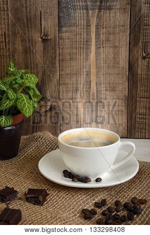 Cup of hot fragrant coffee and coffee beans with chocolate on a mesh fabric. Coffee house. Uplifting mood. Coffee break. Relax. Increasing productivity in the mornings. Coffee breakfast.