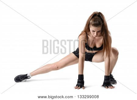 Cut-out portrait of young strong muscular woman making warm-up before training. Stretching legs. Studio portrait. Healthy lifestyle. Fitness and sport. Power of body. Sportswear for training.