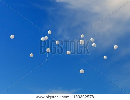 Abstract background. Fifteen white balloons fly up in blue sky with light clouds.