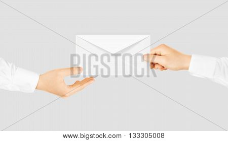 White blank envelope giving hand. Message send presentation. Person taking clear envelope email mockup. Post shipping delivering. Sharing mail message. Sending message men.