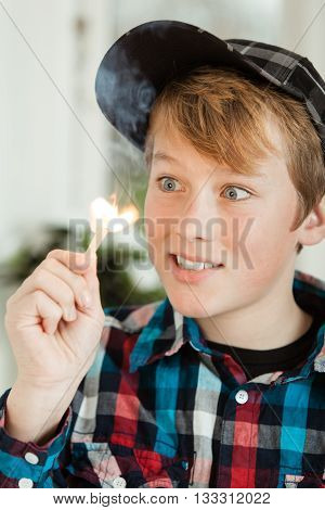 Teenage Boy Mesmerized By Flame Of Lit Match