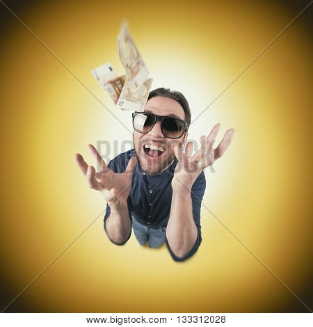 Funny man catch money from above screaming with sun glasses on circle background