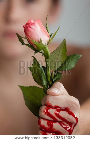 Boy Clutching Pink Rose In Blood Covered Fist
