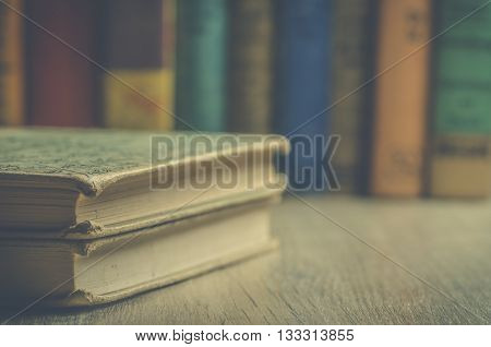 Image of many old books stacked with books in background