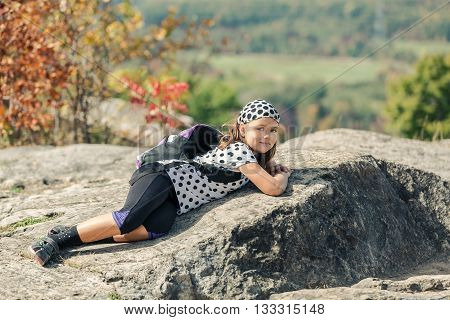 looking tired little happy girl lying and relaxing after hiking on Niagara escarpment stone cliffs, against autumn nature background, on sunny day