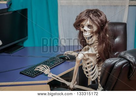 Excited, smiling happy skeleton sitting in chair behind the desktop computer