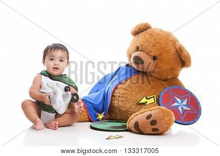 Adorable baby boy dressed as a super hero and sitting in a laundry basket next to a giant, stuffed bear wearing a cape and holding a shield.  Isolated on white.