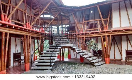 fachada de una casa colonial hecha con palos de bambu y concreto