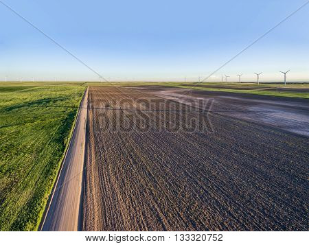 Plowed field, dirt road and windmill farm at Pawnee National Grassland near Grocer, Colorado - early summer aerial view