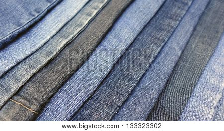 Colorful blue denim jeans overlapped in a diagonal striped pattern with a blurred effect, bluejean blur background photo.