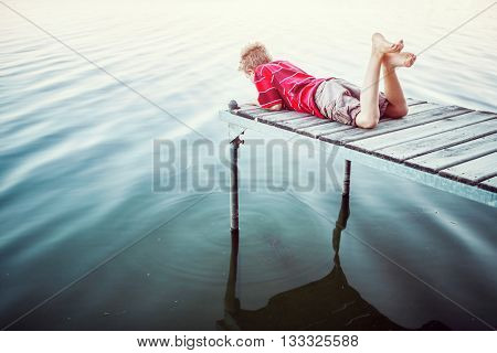 Boy laying on a dock by a lake, vintage toned image.