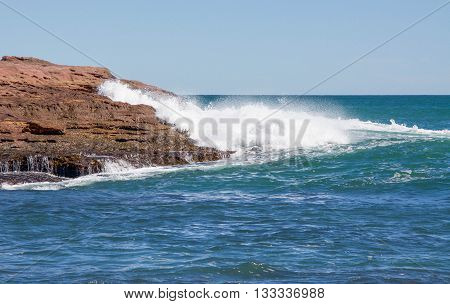 Indian Ocean waves and rugged sandstone rock outcroppings at Pot Alley on a clear day in Kalbarri, Western Australia.