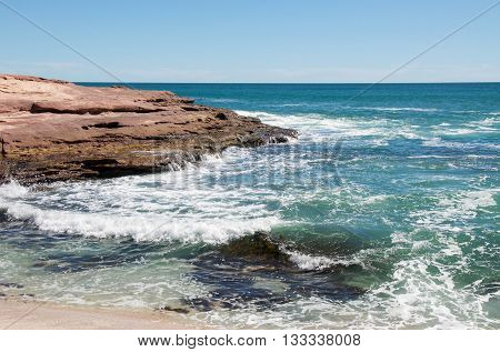 Turquoise Indian Ocean seascape with waves rushing the sandstone rock formations at the secluded cove at Pot Alley under clear blue skies in Kalbarri, Western Australia.