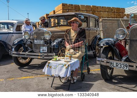 Napier New Zealand - November 19 2014: Drivers and dame dressed in 1930s attire would chauffeur paying passengers around the quaint Art Deco seaside town of Napier on the North Island of New Zealand. Vintage cars are iconic sight of Napier street.