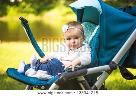 Youmg happy woman playing with her cute baby in summer sunny park outdoor