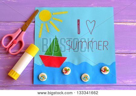 Fun paper holiday card. I love summer. Paper card with sun, ship, sea, fish buttons. Pink scissors, glue. Summer camp idea for kids. Development of children creative skills. Children creativity lesson