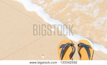 Tropical vacation concept - sandal on a sandy beach