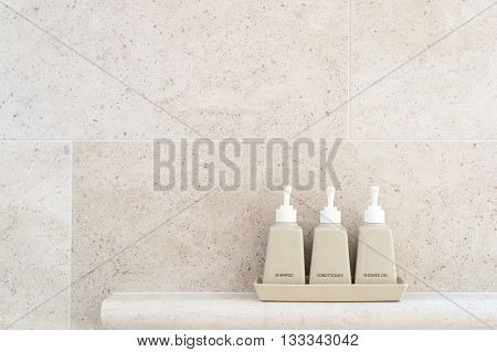 Toiletries tube in a luxury hotel shower gel shampoo and hair conditioner in ceramic ware. Copy space.