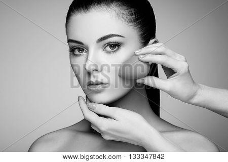 Makeup artist applies skintone. Beautiful woman face. Perfect makeup. Skincare foundation. Sponge makeup artist
