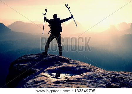 Tourist With  Medicine Crutch Above Head Achieved Mountain Peak. Hiker With Broken Leg In Immobilize