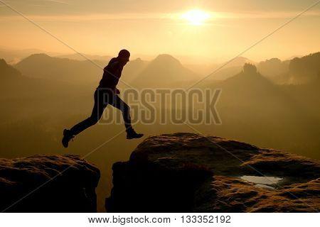 Crazy hiker in black is jumping between rocky peaks. Happy man. Wonderful daybreak in rocky mountains heavy orange mist in deep valley. Miracle of nature poster