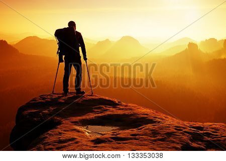 Hiker With Broken Leg In Immobilizer. Deep Misty Valley Bellow Silhouette