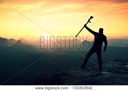 Tourist With Forearm Crutch Above Head Achieved Mountain Peak. Hiker With Broken Leg