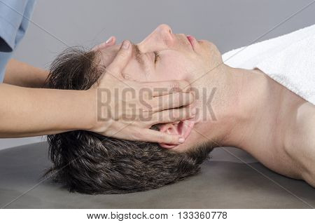 Chiropractor Assessing The Muscles On A Jaw