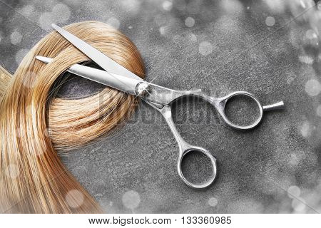 Hairdresser's scissors with strand of blonde hair on grey background poster